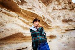 Un homme attirant étreint une belle femme Les paires enveloppées dans le plaid au milieu d'un canyon arénacé Photo libre de droits