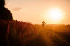 Un homme au coucher du soleil dans un domaine Images stock