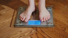 Un homme aux pieds nus mesure son poids sur des échelles d'un plancher Photo stock