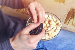 Un homme avec un bol de maïs éclaté et un à télécommande dans sa main regarde la TV sur le sofa Images libres de droits