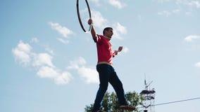 Un homme avec un cercle dans des ses mains est au-dessus de la terre sur un câble en métal Longueur fra?che Playback lent banque de vidéos