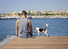 Un homme avec un chien sur le pilier de flottement Image stock