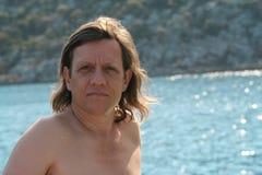 Un homme avec de longs cheveux sur la mer