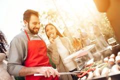 Un homme avec des filles fait frire des saucisses et des légumes sur un barbecue Photographie stock