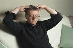 Un homme avec des verres et une chemise noire masse sa tête image libre de droits