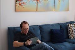 Un homme avec des verres travaille à un comprimé homme détendant dans la chambre se reposant sur le divan Homme attirant intéress photographie stock