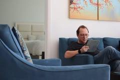 Un homme avec des verres travaille à un comprimé homme détendant dans la chambre se reposant sur le divan Homme attirant intéress image libre de droits