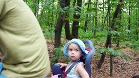 Un homme avec un enfant montant une bicyclette dans la forêt, pendant l'été, l'enfant s'assied dans une chaise spéciale clips vidéos