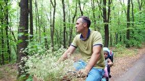 Un homme avec un enfant montant une bicyclette dans la forêt, pendant l'été, l'enfant s'assied dans une chaise spéciale banque de vidéos