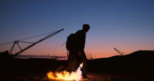 Un homme avec un lance-flammes au coucher du soleil dans le mouvement lent Costume pour l'apocalypse et le Halloween de zombi banque de vidéos