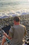 Un homme avec un ordinateur portable travaillant à la plage image stock