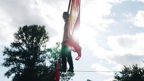 Un homme avec un poteau est sauter très dangereux sur la corde contre le ciel banque de vidéos