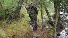 Un homme avec un sac à dos marche le long d'une rivière de montagne banque de vidéos