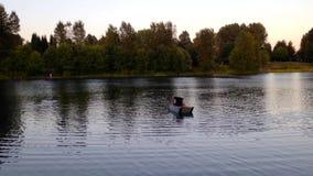 Un homme avec son fils dans un petit canoë à travers les eaux calmes banque de vidéos