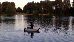Un homme avec son fils dans un petit canoë à travers les eaux calmes clips vidéos