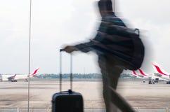 Un homme avec un bagage marche par la salle d'attente d'aéroport Images stock
