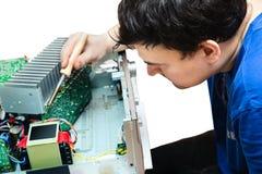 Un homme avec un fer à souder à l'appareil électronique de réparation Photos stock