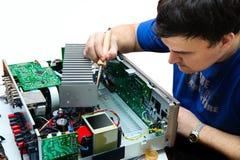 Un homme avec un fer à souder pour réparer le dispositif Photos libres de droits