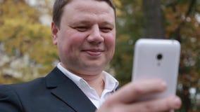 Un homme avec un smartphone de téléphone portable dans des ses mains banque de vidéos