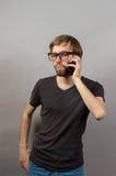 Un homme avec un téléphone portable sur un gris Photos stock