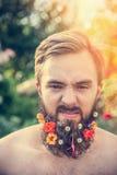Un homme avec un visage fâché avec une barbe avec des fleurs sa barbe sur le fond naturel Images libres de droits