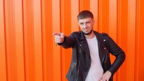Un homme avec une barbe et dans une veste en cuir dirige son doigt à la caméra sur un fond orange, l'espace de copie clips vidéos