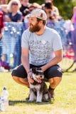 Un homme avec une barbe et son chien en parc à une exposition canine photo libre de droits