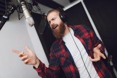 Un homme avec une barbe exécute une chanson dans un studio d'enregistrement Il utilise une chemise de plaid image libre de droits