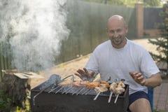 Un homme avec une barbe près du feu et le gril font frire la viande et des saucisses Un jeune homme fait frire un barbecue sur un Image stock