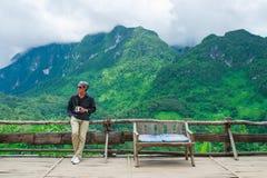 Un homme avec une boisson de café chez Doi Luang Chiang Dao avec le brouillard de pluie Photographie stock libre de droits