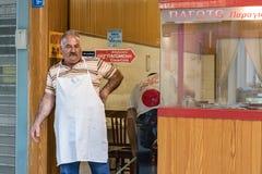 Un homme avec une chemise blanche se penchant sur un mur faisant une pause à l'entrée de son restaurant au centre de la ville à H image libre de droits
