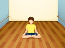 Un homme avec une chemise jaune exécutant le yoga à l'intérieur d'une salle Photographie stock libre de droits