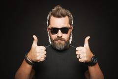 Un homme avec une coiffure élégante et une barbe beaux et forts montre deux pouces dans le studio sur un fond noir Avec l'espace  Images stock