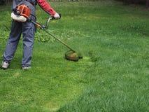 Un homme avec une faucheuse d'essence fauche l'herbe dans le pays image stock