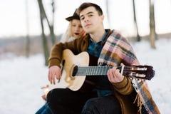 Un homme avec une guitare, tenant des mains avec son moment sensuel atmosphérique d'amie Couples élégants de hippie dans le regar Photos stock