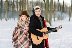 Un homme avec une guitare, tenant des mains avec son moment sensuel atmosphérique d'amie Couples élégants de hippie dans le regar Images libres de droits