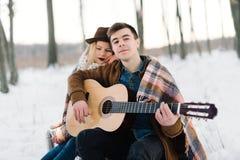Un homme avec une guitare, tenant des mains avec son moment sensuel atmosphérique d'amie Couples élégants de hippie dans le regar Photo stock