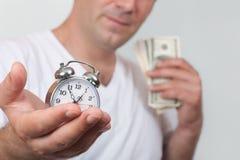 Un homme avec une horloge et un argent Photographie stock libre de droits