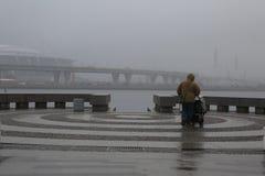 Un homme avec une poussette de bébé sous la pluie sur un secteur de visionnement vide Photo libre de droits