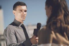 Un homme avec un visage sérieux interviewe une femme Images stock