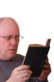Un homme Balding plus âgé affichant un livre noir ou une bible photos libres de droits
