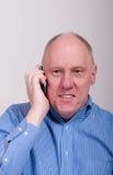 Un homme Balding plus âgé dans la chemise bleue heureuse au téléphone photo libre de droits