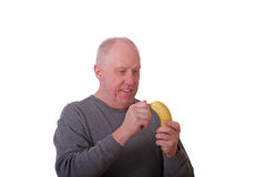 Un homme Balding plus âgé dans la chemise grise enlevant une banane photographie stock