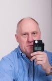 Un homme Balding plus âgé dans la lecture de compteur léger bleue de Shrt photo libre de droits