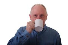 Un homme Balding plus âgé en café potable de chemise bleue photographie stock