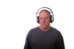 Un homme Balding plus âgé utilisant les écouteurs sans fil photographie stock libre de droits