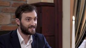 Un homme barbu dans le costume raconte l'histoire avec émotion à l'appareil-photo Représentation des expressions émotives avec de clips vidéos
