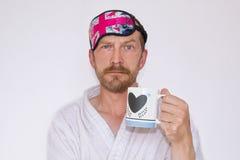 Un homme barbu dans une robe de chambre et un masque à dormir sur sa tête, prises une tasse dans des ses mains photo stock