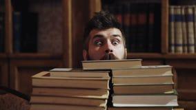 Un homme barbu drôle Homme avec le visage heureux entre les piles des livres dans la bibliothèque, étagères sur le fond L'homme d banque de vidéos