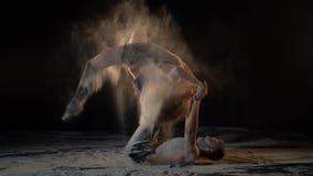 Un homme barbu et une femme dans le crétacé exécutent des tours de yoga d'acro, mouvement lent banque de vidéos